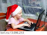 Маленькая девочка в колпаке Санты сидит за компьютером (2011 год). Редакционное фото, фотограф Елена Сикорская / Фотобанк Лори