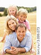 Купить «Счастливая семья из четырех человек лежит на соломе в осеннем поле», фото № 3099073, снято 20 июля 2010 г. (c) Monkey Business Images / Фотобанк Лори