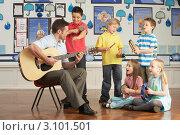 Купить «Учитель играет на гитаре во время урока музыки с детьми», фото № 3101501, снято 6 февраля 2010 г. (c) Monkey Business Images / Фотобанк Лори