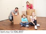 Уставшие родители с двумя детьми в пустой комнате с картонными коробками для переезда. Стоковое фото, фотограф Monkey Business Images / Фотобанк Лори