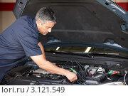 Купить «Автомеханик занимается ремонтом двигателя машины», фото № 3121549, снято 13 мая 2011 г. (c) Monkey Business Images / Фотобанк Лори