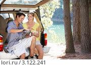 Купить «Молодая пара расположилась на пикник, присев на открытый багажник автомобиля с термосом кофе», фото № 3122241, снято 22 февраля 2011 г. (c) Monkey Business Images / Фотобанк Лори