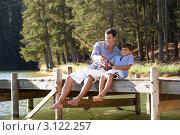 Купить «Отец с сыном тянут удочкой рыбу, сидя на деревянном причале», фото № 3122257, снято 22 февраля 2011 г. (c) Monkey Business Images / Фотобанк Лори