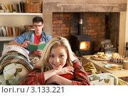 Купить «Молодая пара отдыхает в уютной комнате с камином», фото № 3133221, снято 5 октября 2010 г. (c) Monkey Business Images / Фотобанк Лори