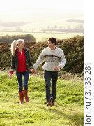 Молодая влюбленная пара гуляет по полю в ясный день. Стоковое фото, фотограф Monkey Business Images / Фотобанк Лори