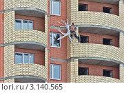 Купить «Рабочий-верхолаз заделывает строительные швы на фасаде новостройки», фото № 3140565, снято 28 декабря 2011 г. (c) Владимир Сергеев / Фотобанк Лори