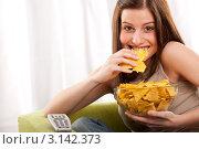 Купить «Молодая девушка ест чипсы перед телевизором», фото № 3142373, снято 16 марта 2009 г. (c) CandyBox Images / Фотобанк Лори