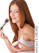 Купить «Улыбающаяся рыжеволосая женщина наносит пудру кистью», фото № 3145693, снято 20 марта 2009 г. (c) CandyBox Images / Фотобанк Лори