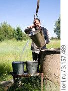 Купить «Мужчина наливает воду в ведра у деревенского колодца», фото № 3157489, снято 1 июля 2011 г. (c) Светлана Кузнецова / Фотобанк Лори