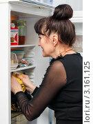 Весёлая женщина средних лет заглядывает в открытый холодильник (2012 год). Редакционное фото, фотограф Игорь Низов / Фотобанк Лори