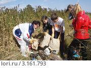 Школьники вместе с учительницей участвуют в акции по очистке берега Амурского залива от мусора (2009 год). Редакционное фото, фотограф Татьяна Беликова / Фотобанк Лори