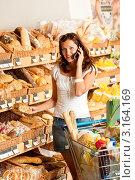 Молодая женщина разговаривает по мобильному телефону в продуктовом супермаркете. Стоковое фото, фотограф CandyBox Images / Фотобанк Лори
