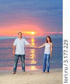Молодая пара держится за руки на песочном пляже на фоне морского заката. Стоковое фото, фотограф Ольга Хорошунова / Фотобанк Лори