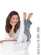 Купить «Улыбающаяся молодая брюнетка лежит на животе перед книгой», фото № 3181169, снято 4 сентября 2009 г. (c) CandyBox Images / Фотобанк Лори