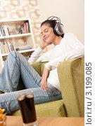 Купить «Молодая брюнетка наслаждается музыкой в наушниках, сидя в кресле», фото № 3199085, снято 9 ноября 2009 г. (c) CandyBox Images / Фотобанк Лори