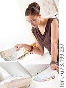Купить «Задумчивая молодая женщина-дизайнер с палитрой цветов смотрит в ноутбук», фото № 3199237, снято 16 ноября 2009 г. (c) CandyBox Images / Фотобанк Лори