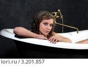 Молодая брюнетка лежит в белой ванной. Стоковое фото, фотограф Елена Сикорская / Фотобанк Лори