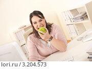 Купить «Деловая женщина грызет на рабочем месте в офисе зеленое яблоко», фото № 3204573, снято 20 января 2010 г. (c) CandyBox Images / Фотобанк Лори