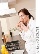 Молодая брюнетка завтракает на кухне, ест тосты. Стоковое фото, фотограф CandyBox Images / Фотобанк Лори