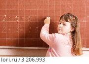 Купить «Серьезная девочка пишет левой рукой на доске», фото № 3206993, снято 13 января 2012 г. (c) Майя Крученкова / Фотобанк Лори