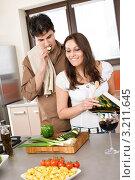 Купить «Парень пробует еду во время приготовления, девушка улыбается», фото № 3211645, снято 30 марта 2010 г. (c) CandyBox Images / Фотобанк Лори