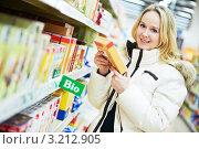 Купить «Молодая женщина в супермаркете выбирает продукты», фото № 3212905, снято 10 февраля 2020 г. (c) Дмитрий Калиновский / Фотобанк Лори