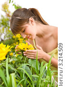 Купить «Молодая женщина вдыхает аромат подсолнуха», фото № 3214509, снято 1 мая 2010 г. (c) CandyBox Images / Фотобанк Лори