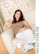 Молодая женщина на диване перед столиком с журналом и кружкой кофе. Стоковое фото, фотограф CandyBox Images / Фотобанк Лори