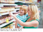 Купить «Молодая женщина с маленьким мальчиком на руках стоит у стеллажа в супермаркете и показывает пальцем на продукты», фото № 3224121, снято 20 января 2018 г. (c) Дмитрий Калиновский / Фотобанк Лори