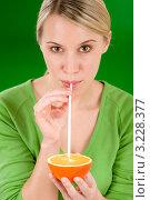 Купить «Красивая девушка пьет сок из апельсина через соломинку», фото № 3228377, снято 4 января 2011 г. (c) CandyBox Images / Фотобанк Лори