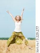 Купить «Счастливая блондинка прыгает в поле пшеницы, подняв руки вверх», фото № 3229277, снято 16 августа 2011 г. (c) Александр Маркин / Фотобанк Лори