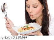 Девушка увлеченно ест спагетти. Стоковое фото, фотограф CandyBox Images / Фотобанк Лори