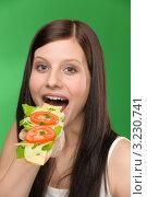Купить «Девушка ест вкусный бутерброд», фото № 3230741, снято 4 февраля 2011 г. (c) CandyBox Images / Фотобанк Лори