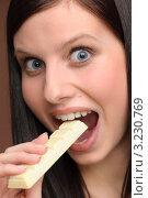 Купить «Девушка кусает кусочек белого шоколада», фото № 3230769, снято 4 февраля 2011 г. (c) CandyBox Images / Фотобанк Лори