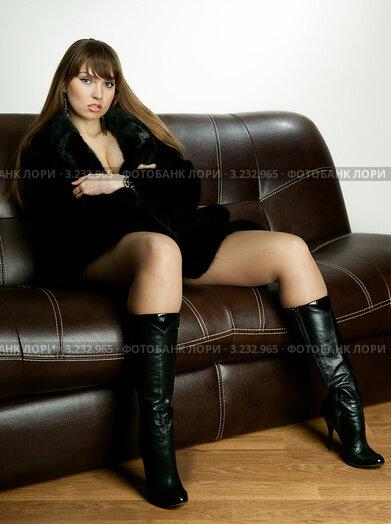 Эротичная девушка в сапогах на диване