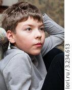 Купить «Мальчик положив руку под голову внимательно смотрит в сторону», эксклюзивное фото № 3234613, снято 4 февраля 2012 г. (c) Игорь Низов / Фотобанк Лори