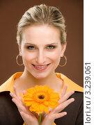 Купить «Девушка в коричневой кофте держит в руках подсолнух», фото № 3239061, снято 23 февраля 2011 г. (c) CandyBox Images / Фотобанк Лори