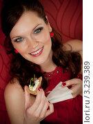 Купить «Улыбающаяся женщина в вечернем платье ест легкую закуску», фото № 3239389, снято 26 февраля 2011 г. (c) CandyBox Images / Фотобанк Лори