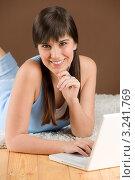 Длинноволосая девушка с челкой лежит на полу с ноутбуком. Стоковое фото, фотограф CandyBox Images / Фотобанк Лори