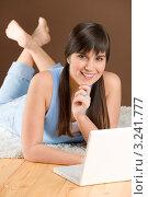 Улыбающаяся длинноволосая девушка с челкой лежит на полу с ноутбуком. Стоковое фото, фотограф CandyBox Images / Фотобанк Лори