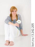 Купить «Молодая женщина сидит на полу с белой герберой», фото № 3242205, снято 17 марта 2011 г. (c) CandyBox Images / Фотобанк Лори