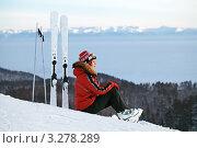 Задумчивая девушка с лыжами сидит на горнолыжном склоне и смотрит вдаль. Стоковое фото, фотограф Игорь Долгов / Фотобанк Лори