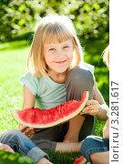 Веселая белокурая девочка ест спелый арбуз на траве в весеннем парке. Стоковое фото, фотограф yarruta / Фотобанк Лори