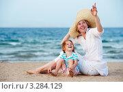 Купить «Молодая женщина в шляпе с ребенком сидят на песчаном пляже», фото № 3284129, снято 22 мая 2018 г. (c) Дмитрий Калиновский / Фотобанк Лори