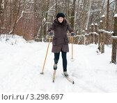 Радостная женщина лыжница на лыжах едет в горку по зимнему лесу. Стоковое фото, фотограф Игорь Низов / Фотобанк Лори
