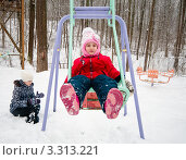 Купить «Маленькая весёлая девочка зимой качается на качелях в детском городке зимой», эксклюзивное фото № 3313221, снято 26 февраля 2012 г. (c) Игорь Низов / Фотобанк Лори