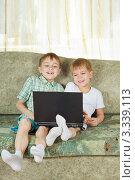 Купить «Два смеющихся мальчика сидят на диване с ноутбуком на коленях», фото № 3339113, снято 9 марта 2012 г. (c) Андрей Щекалев (AndreyPS) / Фотобанк Лори