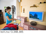Купить «Девушка гладит одежду и смотрит телевизор», фото № 3348385, снято 24 января 2019 г. (c) Erwin Wodicka / Фотобанк Лори