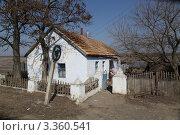 """Дорожный знак """"круговое движение"""" и пожилая женщина  возле одинокого деревенского дома (2012 год). Редакционное фото, фотограф Юрий Кузовлев / Фотобанк Лори"""