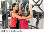 Купить «Девушка-инструктор помогает женщине выполнять упражнение на тренажере», фото № 3367097, снято 31 января 2012 г. (c) CandyBox Images / Фотобанк Лори